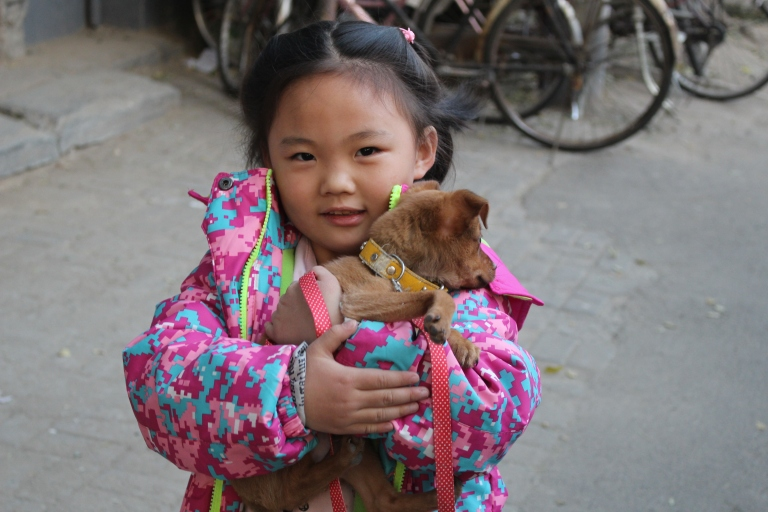 Girl and her dog in the hutongs. Beijing, China