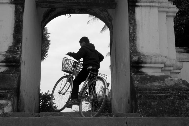 Biking in the monastery walls. Luang Prabang, Laos
